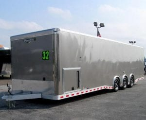 32' aluminum enclosed car trailer with triple spread axles and a generator door